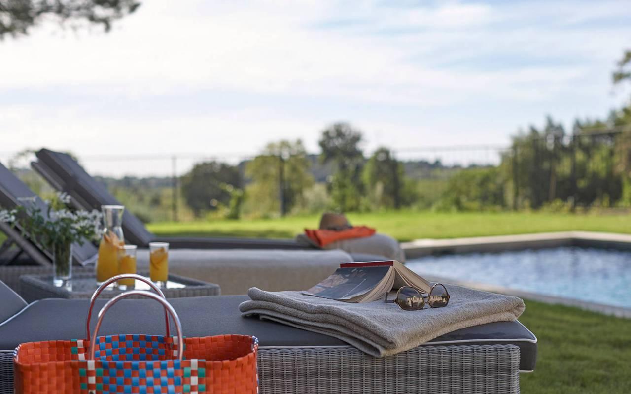 Chaises longues au bord de la piscine dans notre hôtel spa dans l'Hérault, le Château St Pierre de Serjac.